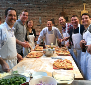 an image of 7 smiling white people standing around a butcher block work table, proudly displaying the 5 pizzas they made